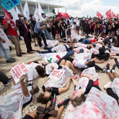Demonstranter ligger på marken i staden Brasilia i protest mot statsledningens hantering av coronapandemin