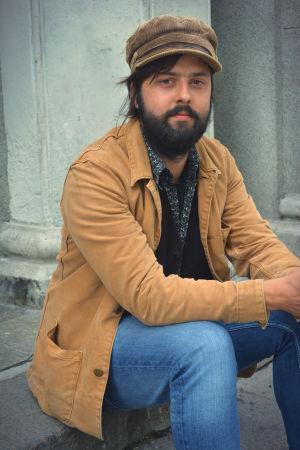 Konstnären Robin Nõgisto sitter på en trappa.
