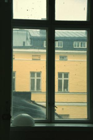 Smutsigt fönster inifrån Lappvikens sjukhus genom vilket man ser en gul fasad på andra sidan av en innergård.