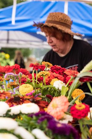 Kukkakuhhauksen myyntikojussa, kukkakimppujen takana, olkihattupäinen nainen järjestelee kukkasia.