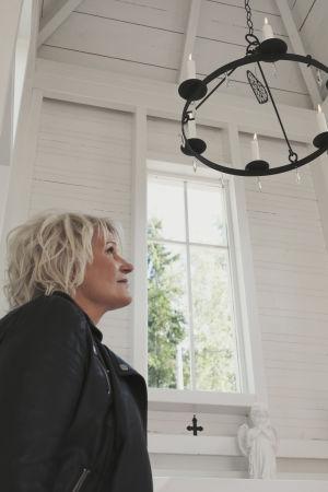 Vaaleahiuksinen nainen valkoiseksi maalatussa puukirkossa, katsoo ylöspäin kohti kattoikkunaa ja mustaa takorautaista kynttiläkruunua joka roikkuu katosta.