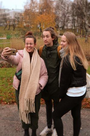 Tre ungdomar, en pojke och två flickor, i en grupp som tar en selfie.