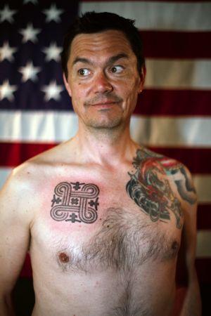 Tatuoitu mies taustalla Amerikan lippu