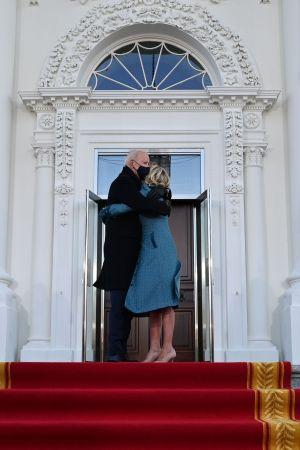 Joe och Jill Biden kramas innan de går in i Vita huset