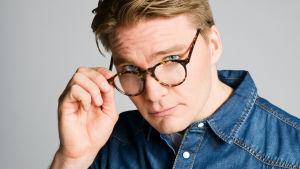 Tommi (Leo Honkonen) katsoo kameraan lasiensa takaa.