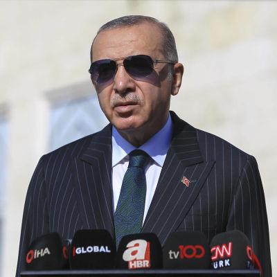 Turkiets president Recep Tayyip Erdogan i solglasögon vid ett talarpodium.