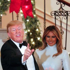 Donald Trump och Melania gör miner vid julfest i Vita huset.
