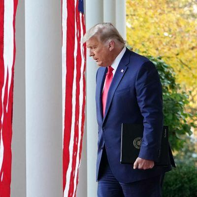 Donald Trump kävelee valkoisen talon edustalla