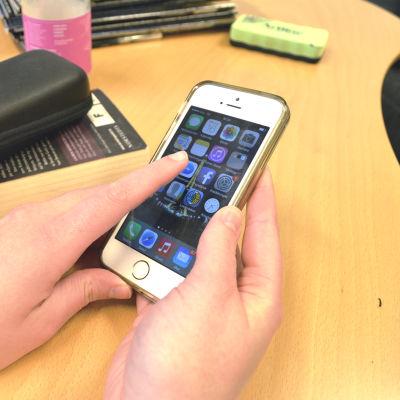 Två händer håller i en mobiltelefon