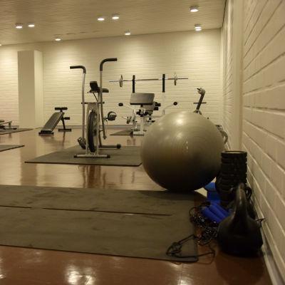 Ett gym med gymnastikmattor på golvet, motionsscyklar och andra motionsredskap.