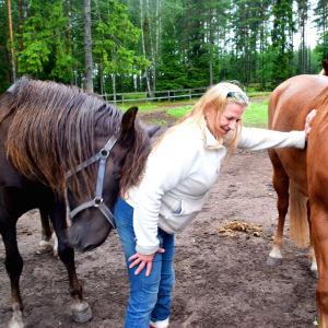 Hästägare blir masserade av en häst och tar stöd mot den andra.