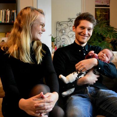 Petronella Nordman och Markus Bergfors sitter i en soffa och skrattar. I famnen håller Markus två månader gamla sonen Roy.