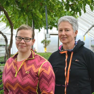 Porträtt av hortonom Leila Roininen och trädgårdsmästare Inger Norrgård som står i ett av Vasa stads växthus för blommor.