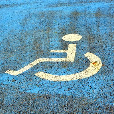 En vit rullstol målad på blått underlag på en parkeringsplats.