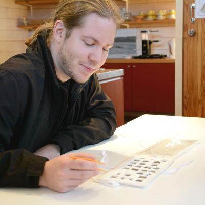 Emil Nygård med pincett i handen och mynt, som han hittat, på bordet.