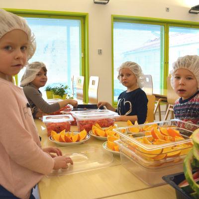 Barn skär upp frukt på daghem.