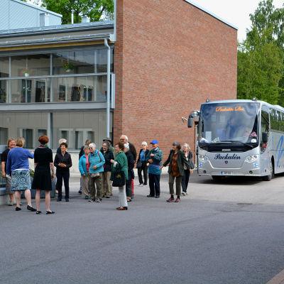 besökarna har stigit ut från bussen och står samlade framför bussen