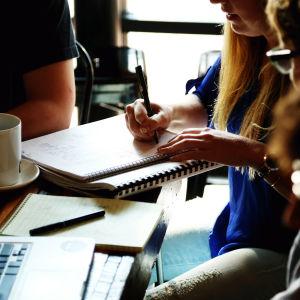 En grupp kollegor har möte runt ett kaffebord.
