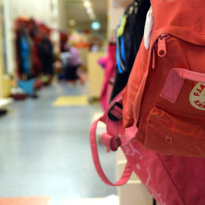 En ryggsäck hänger på en knagg i en skolkorridor.