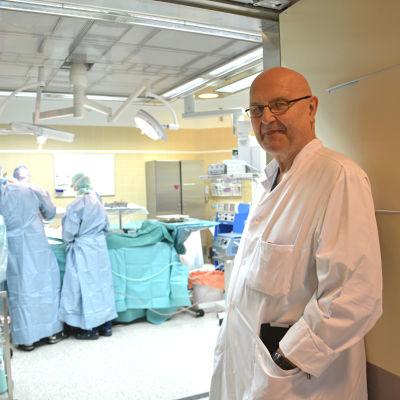 Hjärtkirurg Kalervo Werkkala står vid ingången till en operationssal på Vasa centralsjukhus.