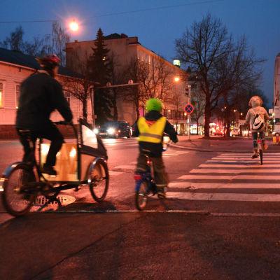 Tre cyklister på gatan