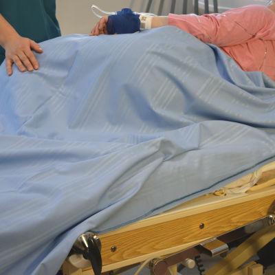 Vårdare brevid patientsäng
