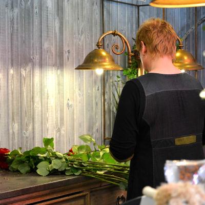 Blomsterhandlare behandlar rosor med ryggen svängd mot kameran