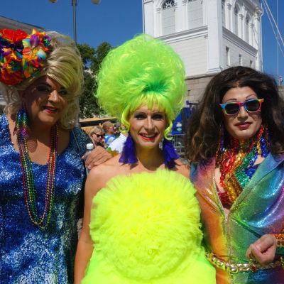 Tre pridedeltagare klädda i färggranna och glittrande kläder och peruker under Helsingfors prideparad 2016.