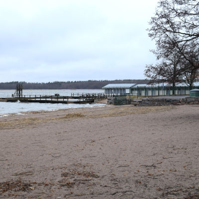 En tom strand. I bakgrunden skymtar en siminrättning.