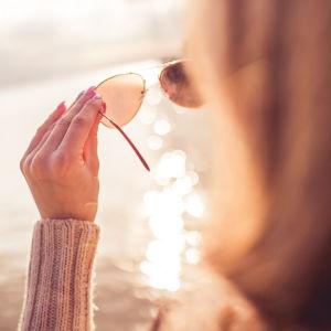 En flicka håller i ett par solglasögon mot solen.