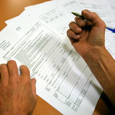 Person fyller i ansökningsblankett.