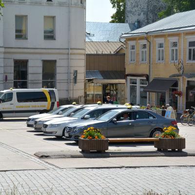 Taxibilar parkerade i en rad på ett torg.