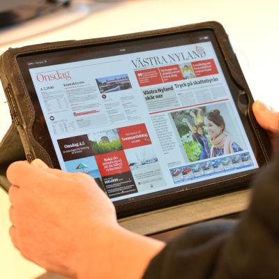 En person läser Västra Nyland på en pekplatta.