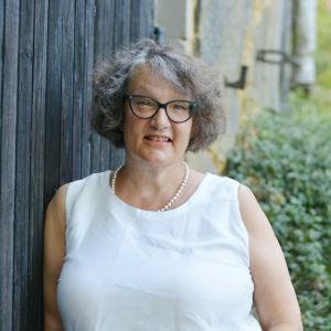 En kvinna står bredvid en svart vägg. Hon har gröna växter bakom sig