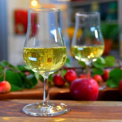 Kaksi lasia siideriä ja punaisia omenoita.