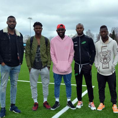 Fem män står på en konstgräsplan.