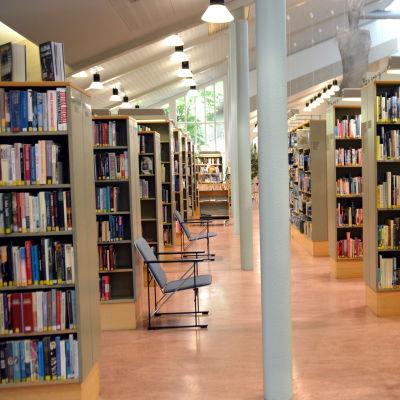 En rad med bokhyllor i ett bibliotek. Orange plastmatta på golvet.