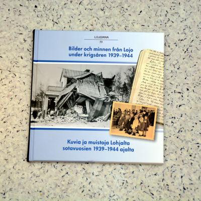 En bok som visar ett sönderbombat hus i Lojo.