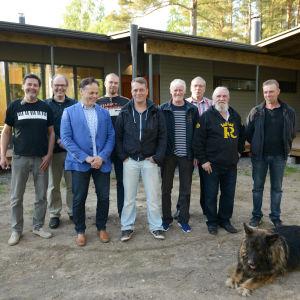 Joukkio miehiä talon edessä