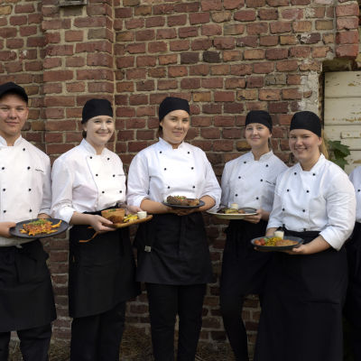Sex kockstuderande står med sina matportioner.