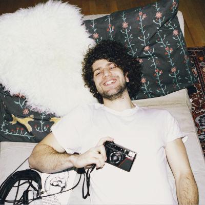 Raivo-artistin promokuva, kiharapäinen mies makaa patjalla hymyillen filmikamera kädessään.