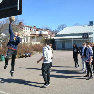 pojkar kastar korgboll på skolgård