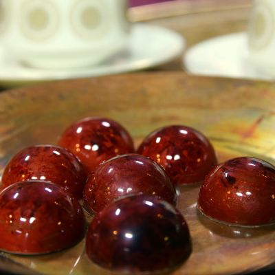 Röda konfekter på en kopparfärgad tallrik.