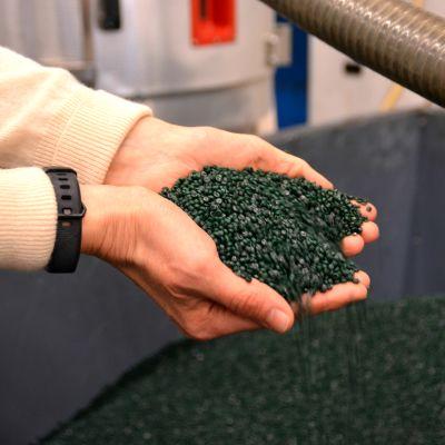 Händer som håller i gröna plastpelletar ovanför ett stort fabrikskärl.