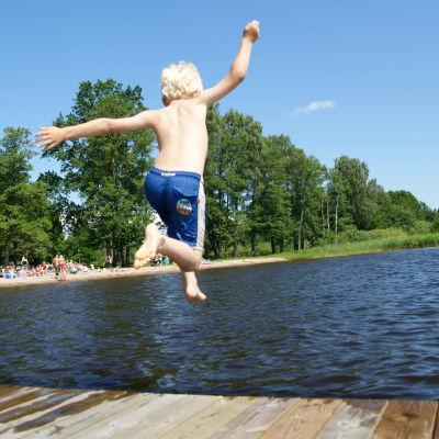 Pojke hoppar i havet.