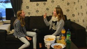 Två flickor sitter på en soffa. Den ena har munnen öppen, den andra har ett popcorn i handen som hon försöker kasta i den första flickans mun.