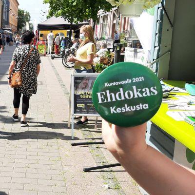 En hand håller på gågatan i Åbo upp en grön reklampins för Centern i samband med kommunalvalet 2021.