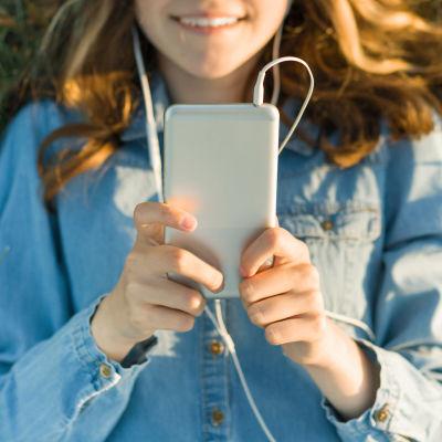 En kvinna ligger på gräset utomhus och tittar på sin mobil med hörlurar i öronen.
