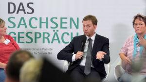 Michael Kretschmer sitter i en panel om talar i en mikrofon.