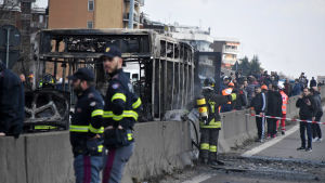 brandmän står framför en uppbränd buss. Två i bildens förgrund och en i bakgrunden.